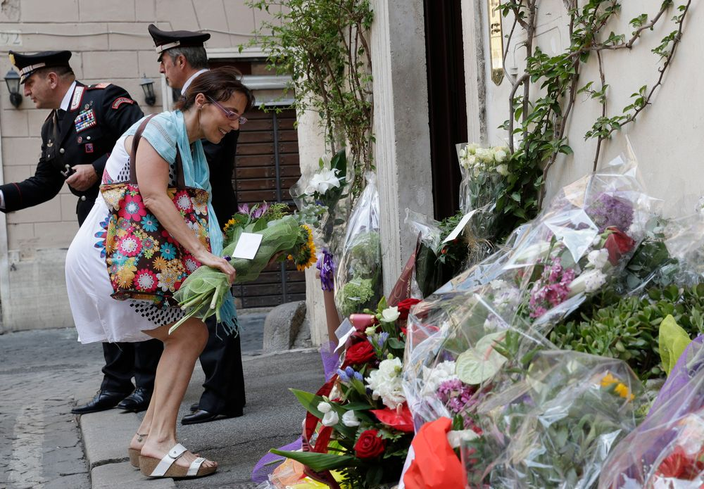 A woman leaves flowers in front of the Carabinieri station where Mario Cerciello Rega was based, in Rome, Saturday, July 27, 2019. In a statement Saturday, Carabinieri officers investigating the death Friday of officer Cerciello Rega, 35, said two American turists, both 19, have been detained for alleged murder and attempted extortion. (AP Photo/Andrew Medichini)