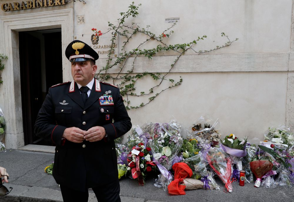 Sandro Ottaviani, commander of the station, stands near flowers left by Roman citizens in front of the Carabinieri station where Mario Cerciello Rega was based, in Rome, Saturday, July 27, 2019. In a statement Saturday, Carabinieri officers investigating the death Friday of officer Cerciello Rega, 35, said two American turists, both 19, have been detained for alleged murder and attempted extortion. (AP Photo/Andrew Medichini)