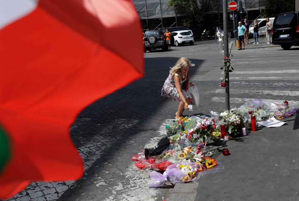 A woman leaves a note in memory on the spot where Mario Cerciello Rega was stabbed to death, in Rome, Saturday, July 27, 2019. In a statement Saturday, Carabinieri officers investigating the death Friday of officer Cerciello Rega, 35, said two American turists, both 19, have been detained for alleged murder and attempted extortion. (AP Photo/Andrew Medichini)