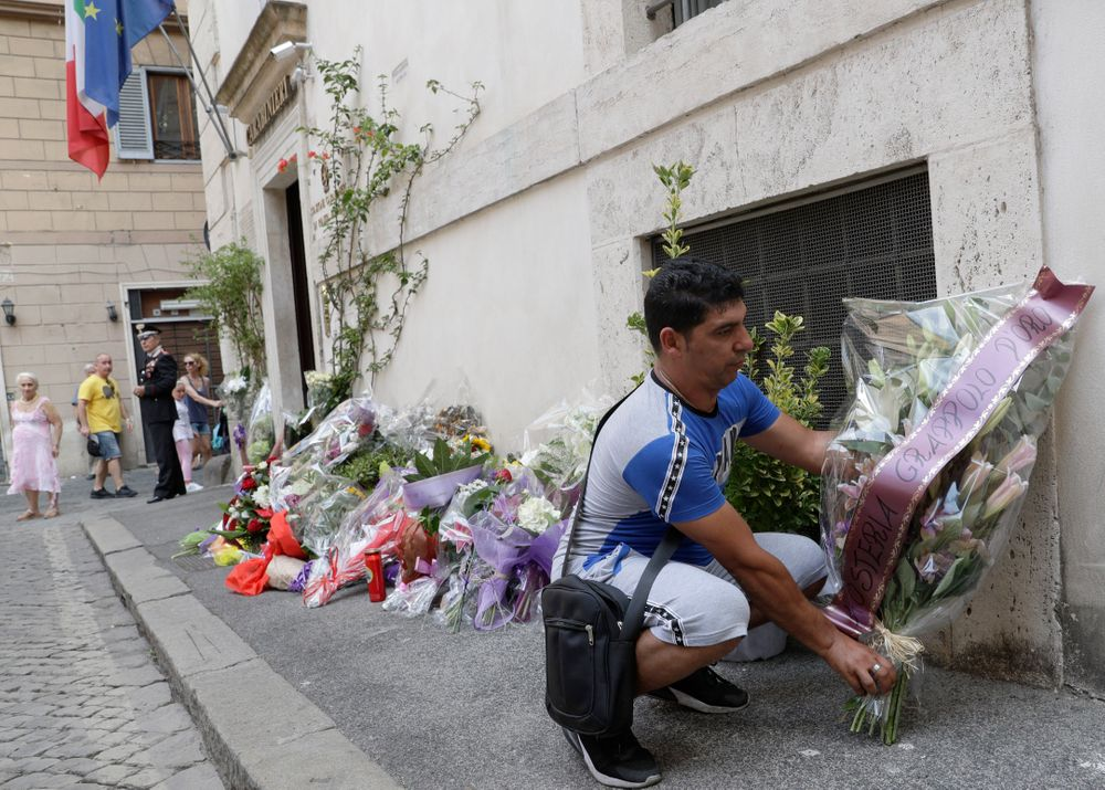 A man leaves flowers in front of the Carabinieri station where Mario Cerciello Rega was based, in Rome, Saturday, July 27, 2019. In a statement Saturday, Carabinieri officers investigating the death Friday of officer Cerciello Rega, 35, said two American turists, both 19, have been detained for alleged murder and attempted extortion. (AP Photo/Andrew Medichini)