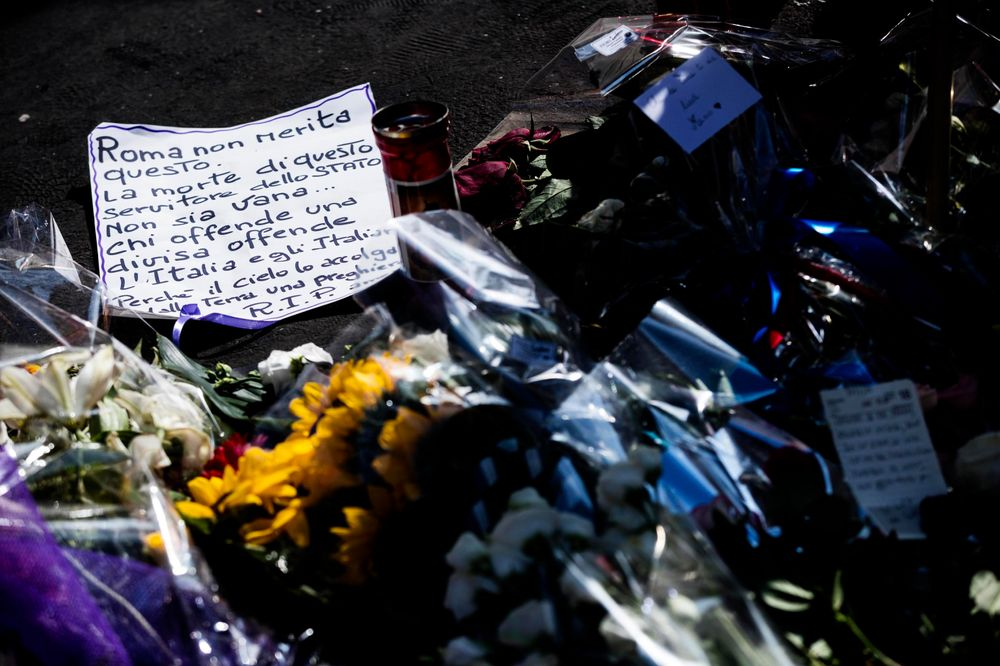 Flowers and messages are left on the spot, in Rome, Saturday, July 27, 2019, where Carabinieri officer Mario Cerciello Rega was stabbed to death early Friday. In a statement Saturday, Carabinieri officers investigating the death of Cerciello Rega, 35, said two young American tourists have been detained for alleged murder and attempted extortion. Ticket at left reads in Italian: