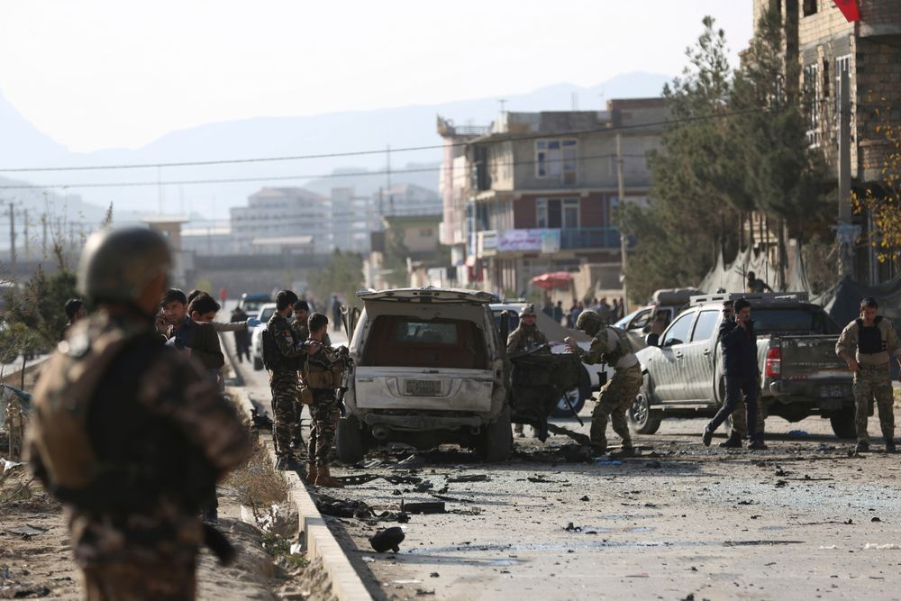 Foreign and local security personnel gather at the site of car bomb attack in the Kabul, Afghanistan, Wednesday, Nov. 13, 2019. A car bomb detonated in the Afghan capital during Wednesday's morning commute, killing seven people and wounding at least seven, officials said. (AP Photo/Rahmat Gul)