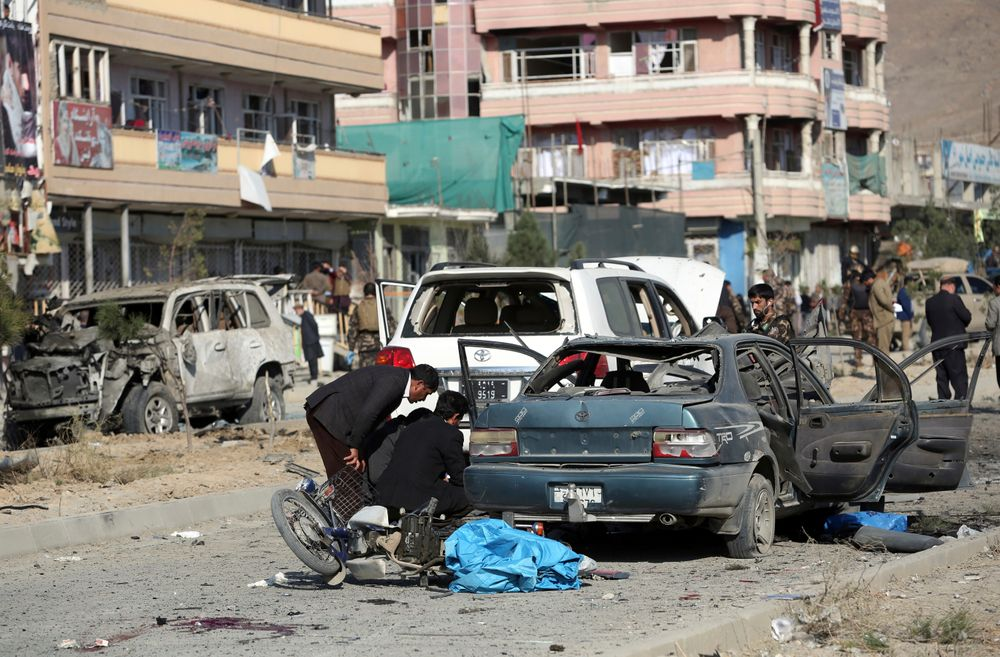 Security personnel gather at the site of car bomb attack in Kabul, Afghanistan, Wednesday, Nov. 13, 2019. A car bomb detonated in the Afghan capital during Wednesday's morning commute killing seven people and wounding at least seven, officials said. (AP Photo/Rahmat Gul)