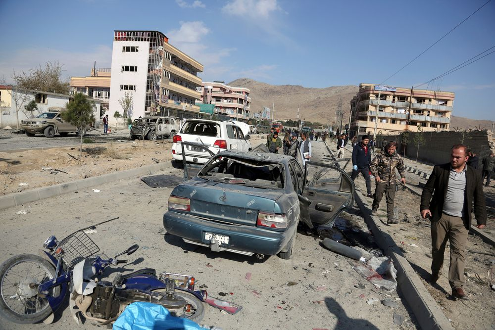 Afghan security personnel gather at the site of a car bomb attack in Kabul, Afghanistan, Wednesday, Nov. 13, 2019. A car bomb detonated in the Afghan capital of Kabul during Wednesday's morning commute, killing several people, officials said. (AP Photo/Rahmat Gul)