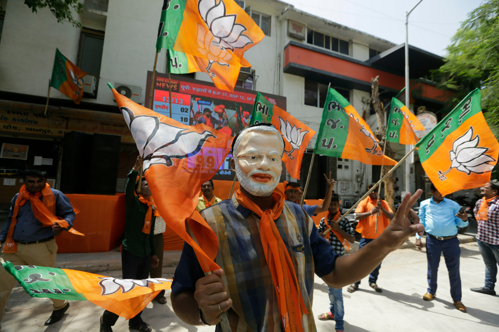 A supporters of India's ruling Bharatiya Janata Party wears mask of Indian Prime Minister Narendra Modi as he celebrates early trends of party's victory in general elections in Ahmadabad, India, Thursday, May 23, 2019.  Modi and his party were off to an early lead as vote counting began Thursday following the conclusion of the country's 6-week-long general election, sending the stock market soaring in anticipation of another five-year term for the Hindu nationalist leader. (AP Photo/Ajit Solanki)