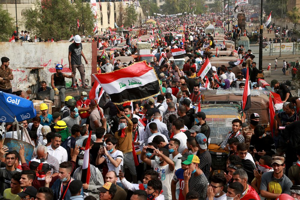 Anti-government protesters march close to the Joumhouriya Bridge that leads to the Green Zone government area, during ongoing protests in Baghdad, Iraq, Sunday, Nov. 3, 2019. (AP Photo/Hadi Mizban)