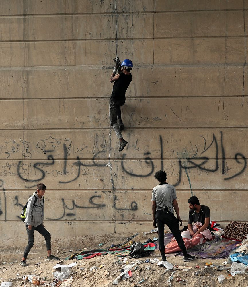 "An anti-government protester climbs the Joumhouriya Bridge that leads to the Green Zone government area, during ongoing protests in Baghdad, Iraq, Sunday, Nov. 3, 2019. Arabic reads, ""Iraq is Iraqi."" (AP Photo/Hadi Mizban)"