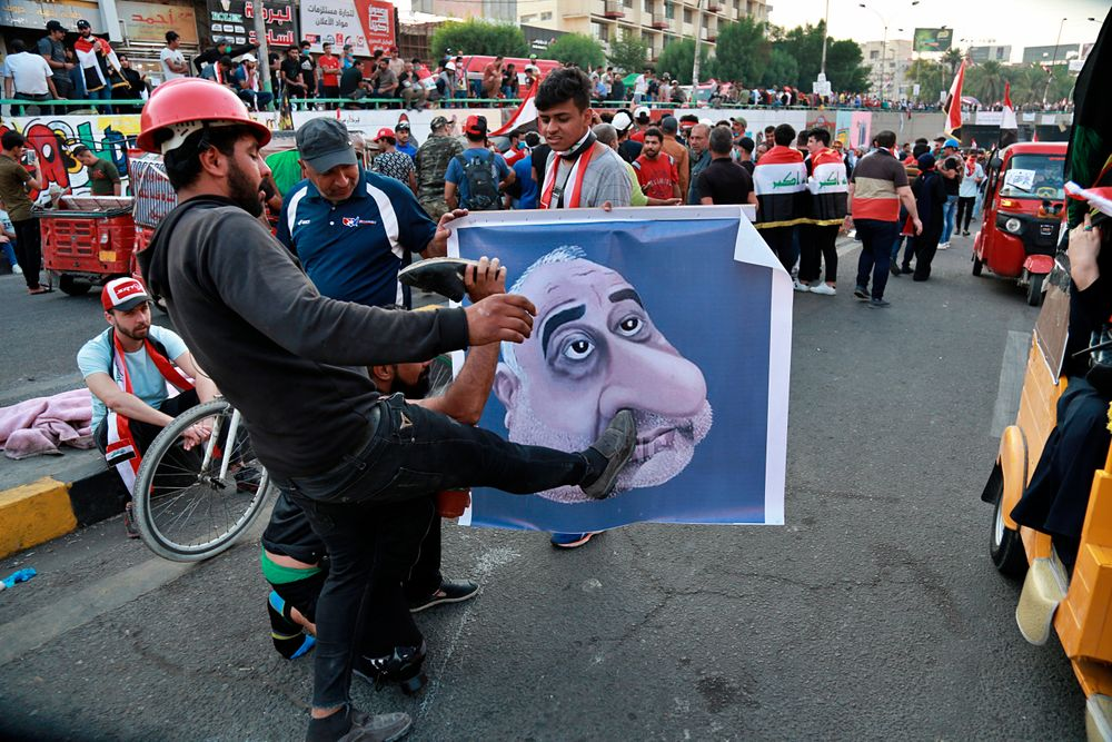 Protesters hit a poster showing Iraqi Prime Minister Adel Abdel-Mahdi with shoes during ongoing anti-government protests in Baghdad, Iraq, Sunday, Nov. 3, 2019. (AP Photo)