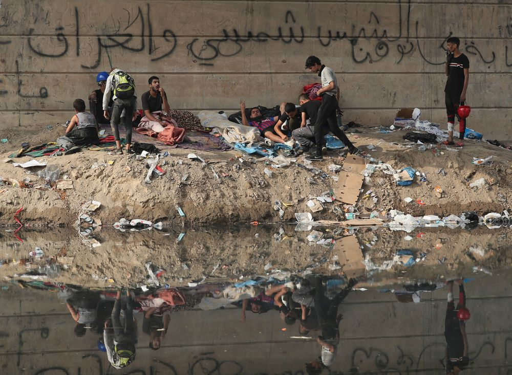 Protesters rest under the Joumhouriya Bridge, that leads to the Green Zone where many government offices and embassies are located, during ongoing anti-government protests, in Baghdad, Iraq, Sunday, Nov. 3, 2019. (AP Photo/Hadi Mizban)