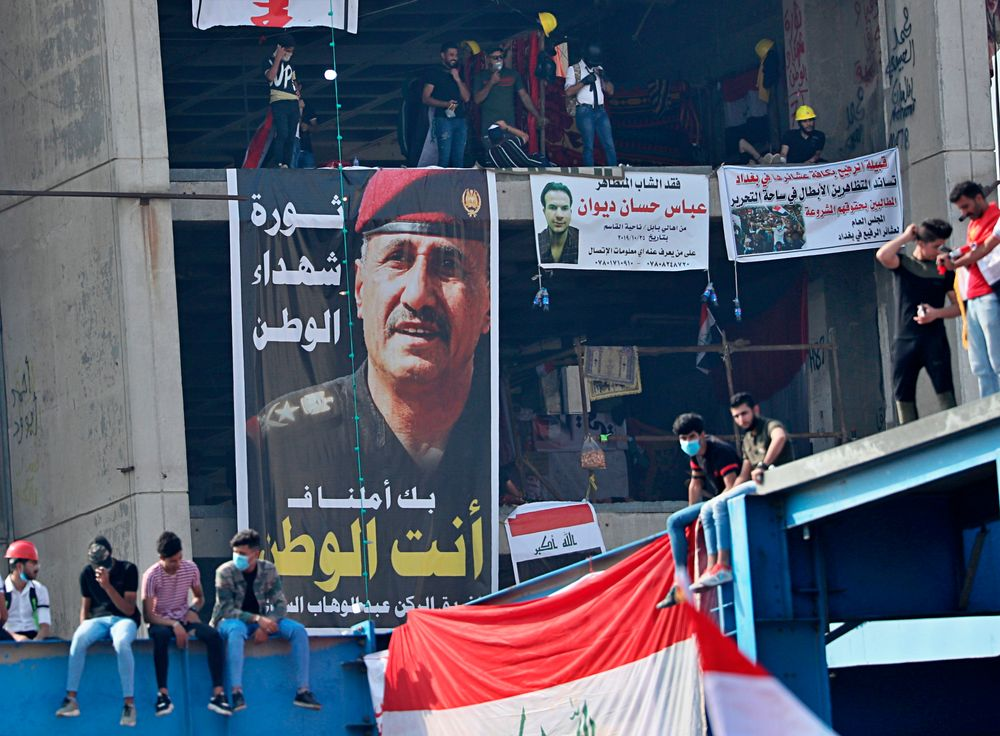 Posters of protesters who have died in anti-government demonstrations and a poster of Lt. Gen. Abdul-Wahab al-Saadi, left, the former commander of the country's elite counterterrorism forces whose dismissal sparked protests about a month ago, hang on a building near Tahrir Square, in Baghdad, Iraq, Sunday, Nov. 3, 2019. (AP Photo/Hadi Mizban)