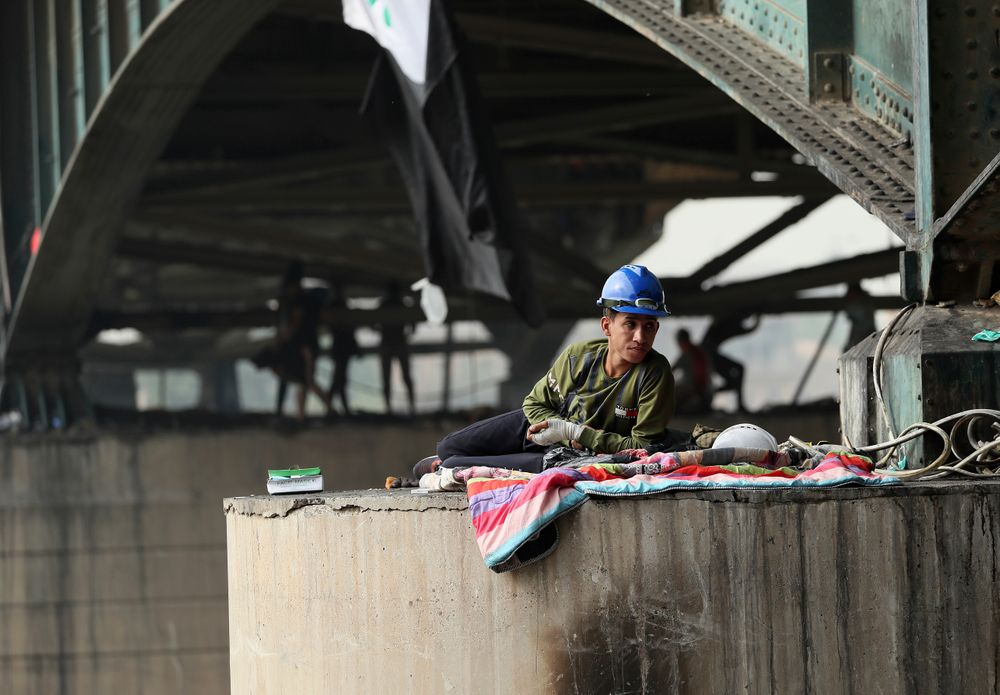 A protesters rest under the Joumhouriya Bridge, that leads to the Green Zone where many government offices and embassies are located, during ongoing anti-government protests, in Baghdad, Iraq, Sunday, Nov. 3, 2019. (AP Photo/Hadi Mizban)