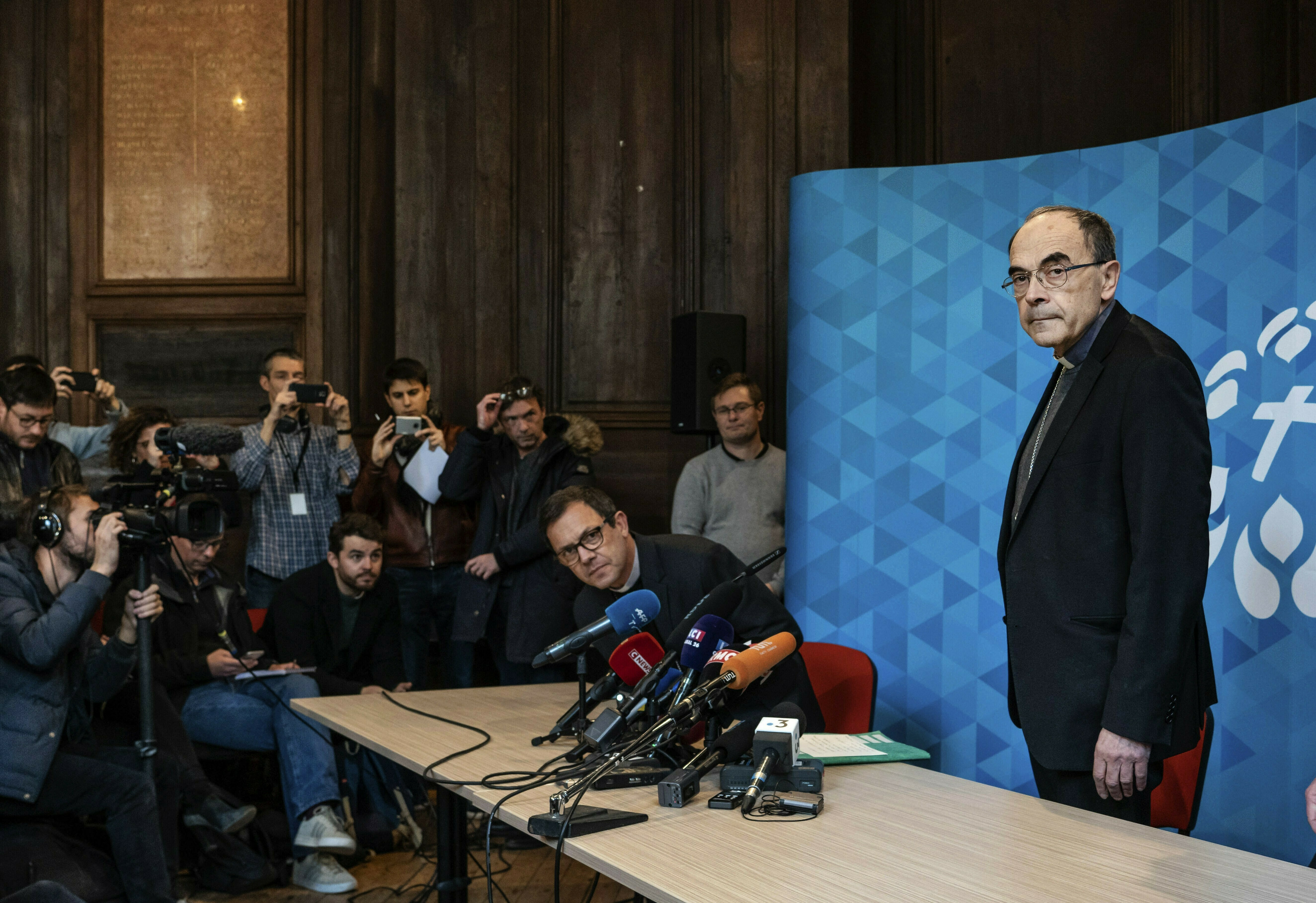 French Cardinal Philippe Barbarin, right, arrives for a press conference in Lyon, central France, Thursday, March 7, 2019. Barbarin offers his resignation to the Pope after a court on Thursday found him guilty of failing to report to authorities allegations of sexual abuse of minors by a priest. (AP Photo/Laurent Cipriani)