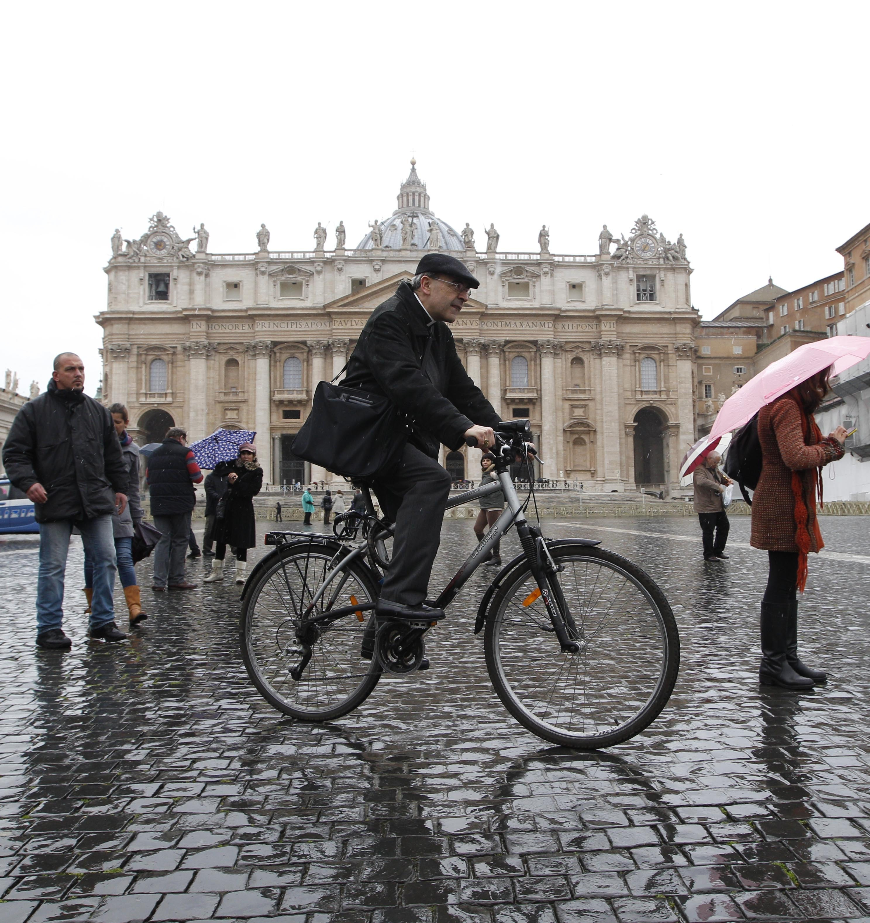 FILE - In this Friday, March 8, 2013 file photo, French Cardinal Philippe Barbarin rides his bicycle in St. Peter's Square after a meeting at the Vatican.  A French court has found top Catholic official Cardinal Philippe Barbarin guilty for failing to report to justice accusations against a pedophile priest. In a surprise decision Thursday, March 7, 2019 in France's most important church sex abuse trial, the Lyon court handed Barbarin a six-month suspended prison sentence for not reporting the facts in the period between July 2014 and June 2015. (AP Photo/Alessandra Tarantino, File )
