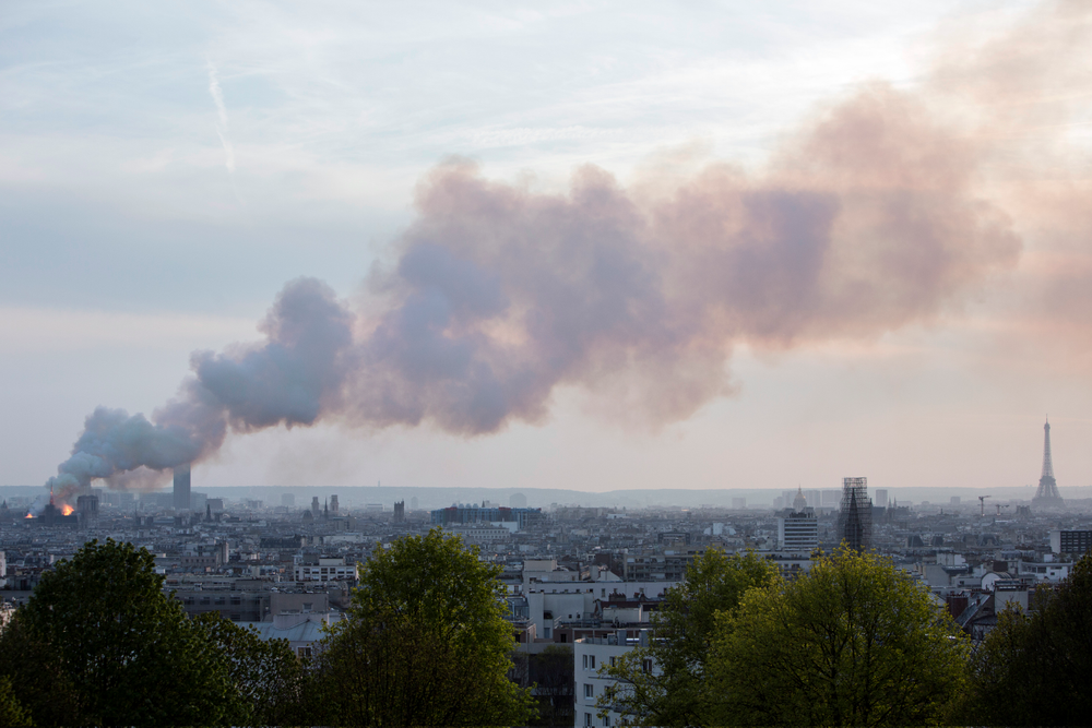 Smoke fill the air as Notre Dame cathedral is burning in Paris, Monday, April 15, 2019. Massive plumes of yellow brown smoke is filling the air above Notre Dame Cathedral and ash is falling on tourists and others around the island that marks the center of Paris. (AP Photo/Rafael Yaghobzadeh)