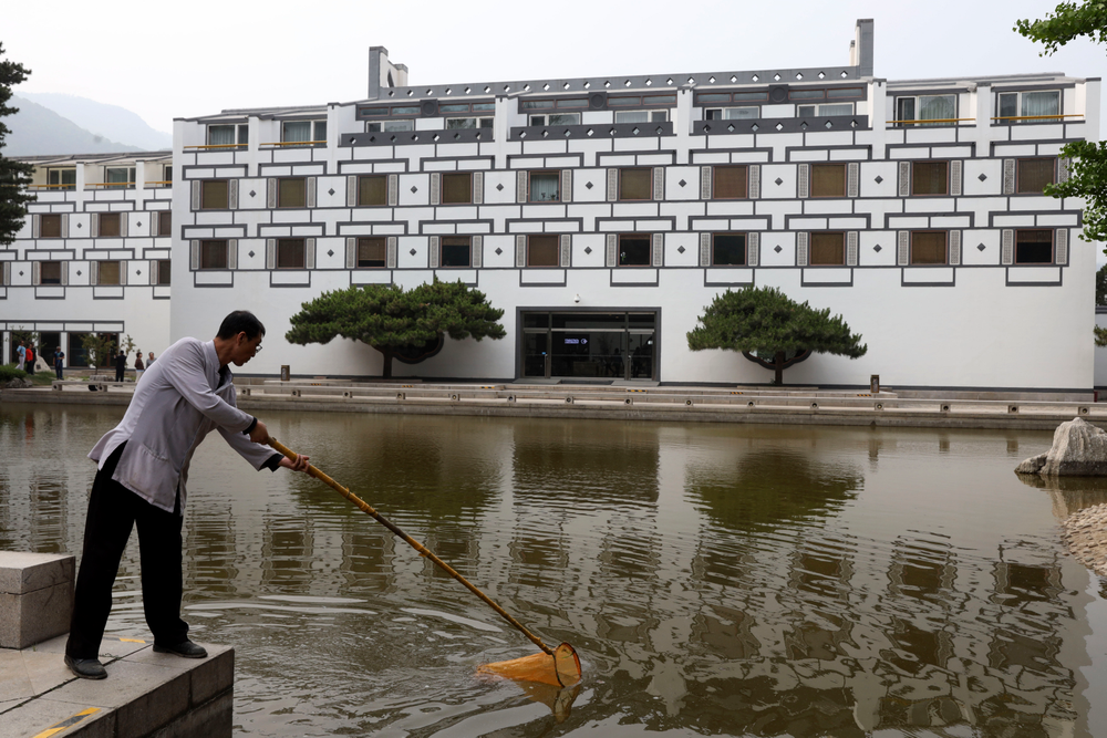 A worker cleans the pond at the Xiangshan hotel designed by Chinese-American architect I.M. Pei and built in 1982 in Beijing, China on Friday, May 17, 2019. Pei, the globe-trotting architect who revived the Louvre museum in Paris with a giant glass pyramid and captured the spirit of rebellion at the multi-shaped Rock and Roll Hall of Fame, has died at age 102, a spokesman confirmed Thursday. (AP Photos/Ng Han Guan)