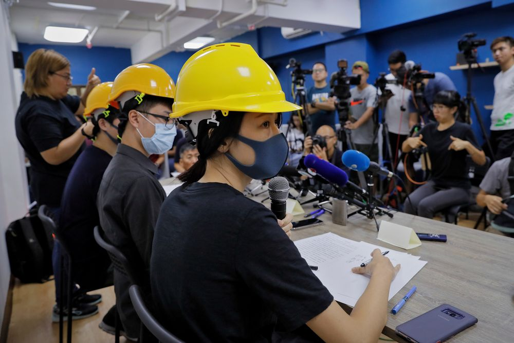Protesters from right, Mary Tsang, Linus Kim and Jerry Chan listen to a question from a reporter during a press conference in Hong Kong, Tuesday, Aug. 6, 2019. Hong Kong protesters Tuesday condemned what they called the government's