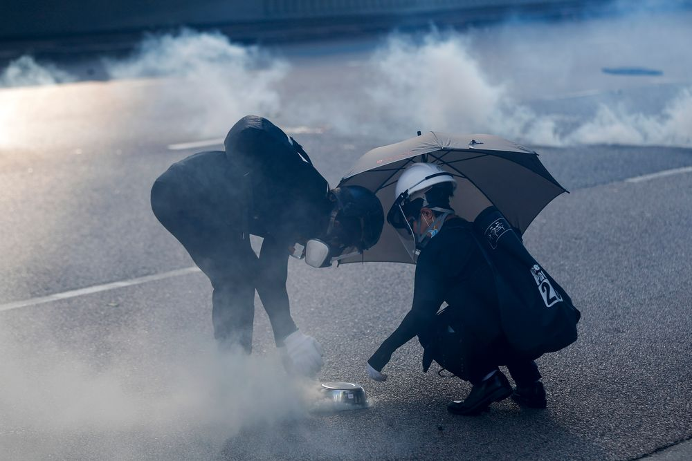 Protester use a plate to cover a tear gas canister fired by riot police as they face off near the Legislative Council building and the Central Government building in Hong Kong, Monday, Aug. 5, 2019. Droves of protesters filled public parks and squares in several Hong Kong districts on Monday in a general strike staged on a weekday to draw more attention to their demands. (AP Photo/Vincent Thian)