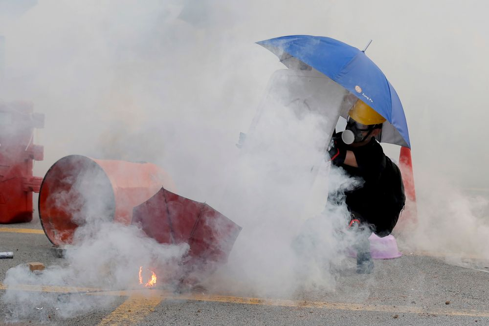 A protester is shrouded by tear gas in Hong Kong, Monday, Aug. 5, 2019. Droves of protesters filled public parks and squares in several Hong Kong districts on Monday in a general strike staged on a weekday to draw more attention to their demands that the semi-autonomous Chinese city's leader resign.(AP Photo/Kin Cheung)