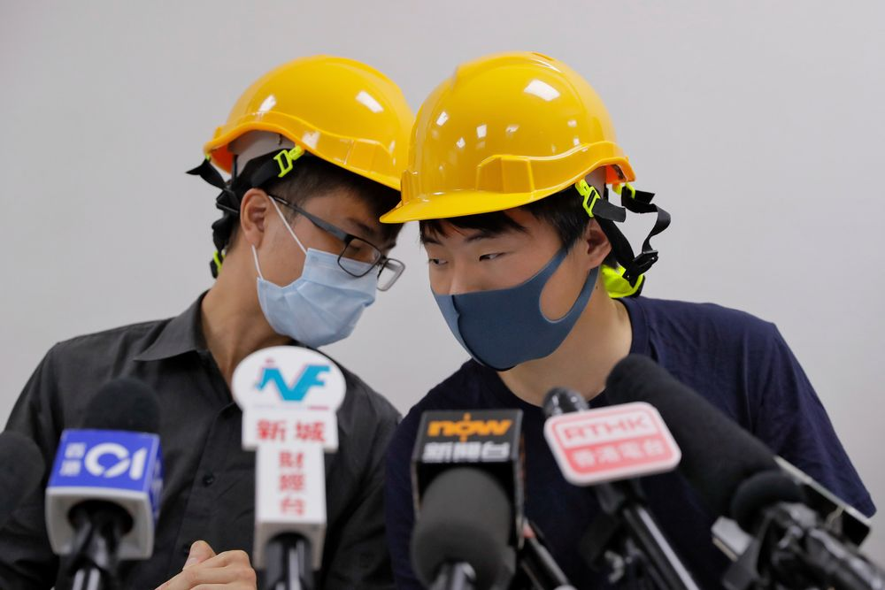 Protesters Jerry Chan, right, chats with Linus Kim during a press conference in Hong Kong, Tuesday, Aug. 6, 2019. Hong Kong protesters Tuesday condemned what they call the government's