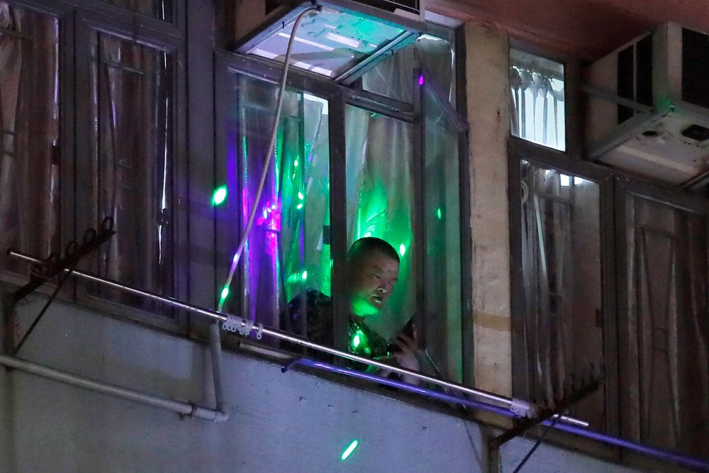 Protesters flash laser beams onto a man in a residential building as they think he is a pro-Beijing supporter in Hong Kong, Monday, Aug. 5, 2019. Droves of protesters filled public parks and squares in several Hong Kong districts on Monday in a general strike staged on a weekday to draw more attention to their demands that the semi-autonomous Chinese city's leader resign.(AP Photo/Kin Cheung)