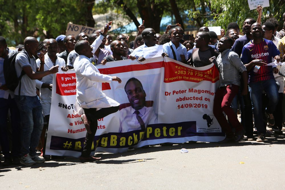 Zimbabwean doctors sing and dance as they protest in Harare, Wednesday, Sept, 18, 2019. Zimbabwean doctors protesting the alleged abduction of a union leader were met by a line of baton- wielding police in the capital as fears grow about government repression. (AP Photo/Tsvangirayi Mukwazhi)