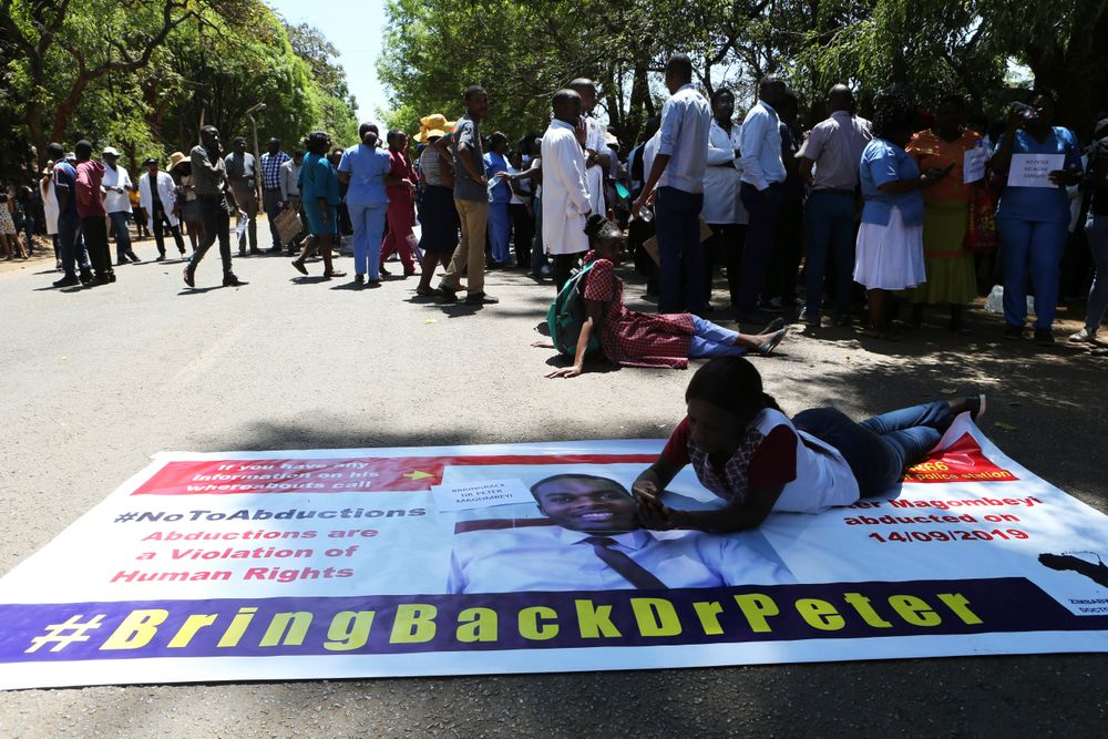 A Zimbabwean doctor lays on a banner with a portrait of fellow missing doctor, Peter Magombeyi, in Harare, Wednesday, Sept, 18, 2019. Zimbabwean doctors protesting the alleged abduction of a union leader were met by a line of baton- wielding police in the capital as fears grow about government repression. (AP Photo/Tsvangirayi Mukwazhi)