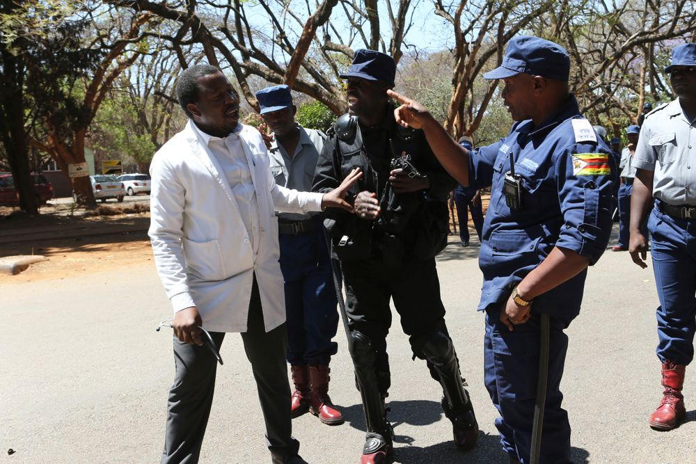 A Zimbabwean doctor is told to retreat after attempting to march in Harare, Wednesday, Sept, 18, 2019. Zimbabwean doctors protesting the alleged abduction of a union leader were met by a line of baton- wielding police in the capital as fears grow about government repression. (AP Photo/Tsvangirayi Mukwazhi)