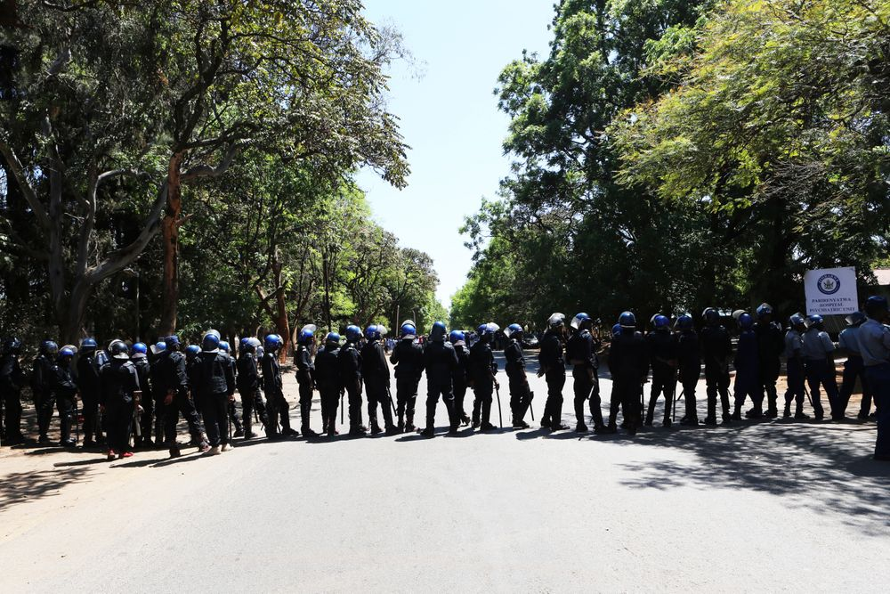 Armed riot police block the road as doctors attempt to march in Harare, Wednesday, Sept, 18, 2019. Zimbabwean doctors protesting the alleged abduction of a union leader were met by a line of baton- wielding police in the capital as fears grow about government repression. (AP Photo/Tsvangirayi Mukwazhi)