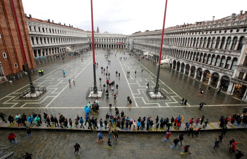 People walk in a flooded St. Mark's Square in Venice, Italy, Tuesday, Nov. 12, 2019. The high tide reached a peak of 127cm (4.1ft) at 10:35am while an even higher level of 140cm(4.6ft) was predicted for later Tuesday evening. (AP Photo/Luca Bruno)