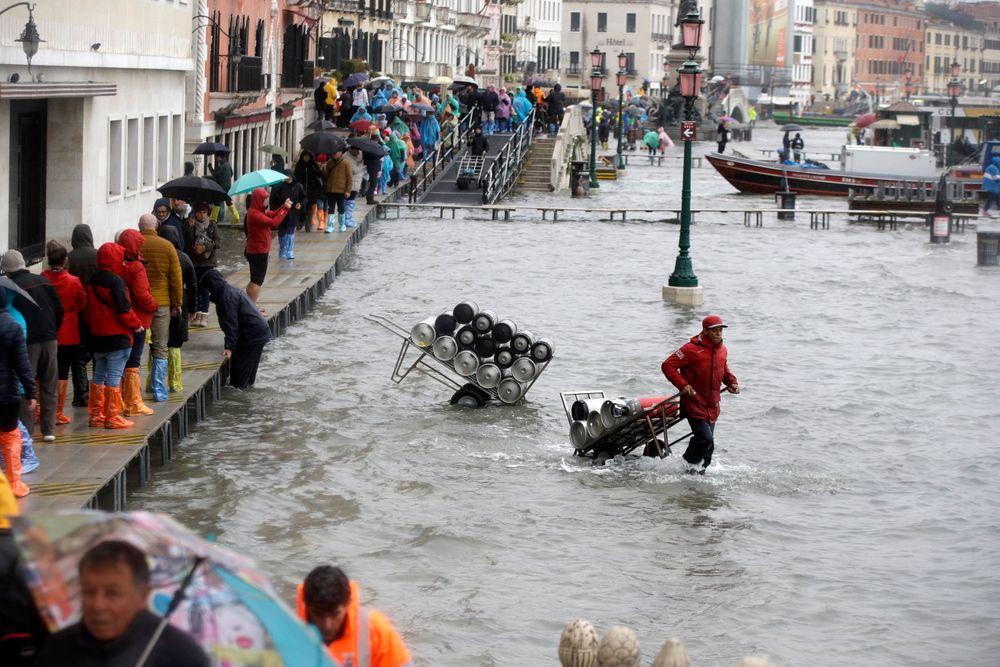 People walk on catwalks set up on the occasion of a high tide, in a flooded Venice, Italy, Tuesday, Nov. 12, 2019. The high tide reached a peak of 127cm (4.1ft) at 10:35am while an even higher level of 140cm(4.6ft) was predicted for later Tuesday evening. (AP Photo/Luca Bruno)