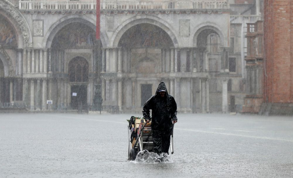 A greengrocer carries his cart as the water begins to flood St. Mark's Square on the occasion of a high tide, in Venice, Italy, Tuesday, Nov. 12, 2019. The high tide reached a peak of 127cm (4.1ft) at 10:35am while an even higher level of 140cm(4.6ft) was predicted for later Tuesday evening. (AP Photo/Luca Bruno)