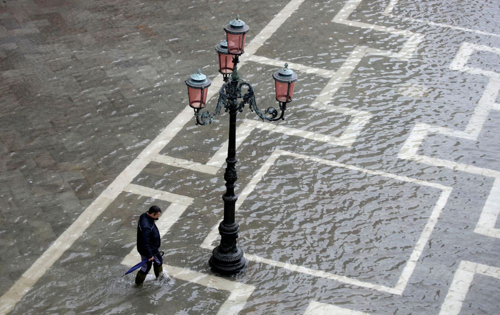 A man walks in a flooded St. Mark's Square in Venice, Italy, Tuesday, Nov. 12, 2019. The high tide reached a peak of 127cm (4.1ft) at 10:35am while an even higher level of 140cm(4.6ft) was predicted for later Tuesday evening. (AP Photo/Luca Bruno)