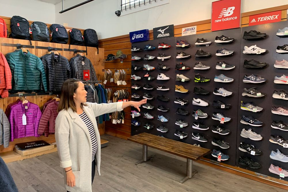 In this photo taken Wednesday, Aug. 28, 2019, Jennifer Lee, whose family owns Footprint shoe store in San Francisco, points to a wall of athletic shoes, many of which are made in China and will be subject to new U.S. tariffs on Chinese goods starting Sept 1. (AP Photo/Terry Chea)