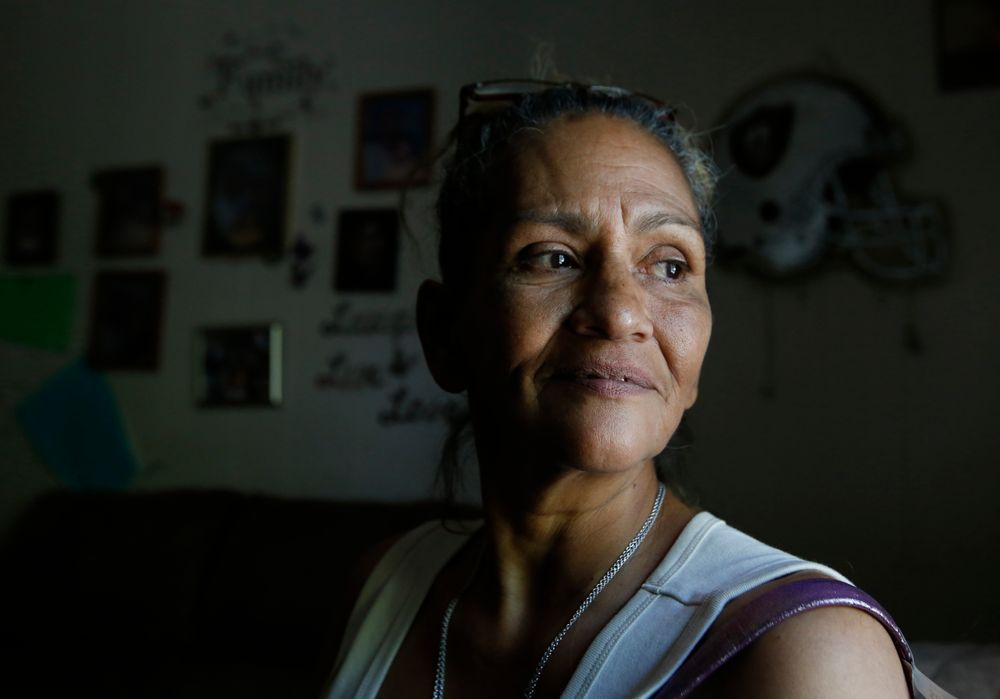 In this photo taken Wednesday, Aug. 14, 2019, Susie Garza who receives a monthly city provided debit card through a trial program, poses in her home in Stockton, Calif. Garza is participating in the Stockton Economic Empowerment Demonstration. The program, which started in February, gives $500 a month to 125 people who earn at or below the median household income of $46,033. They can spend the money with no restrictions. Stockton Mayor Michael Tubbs, who initiated the privately funded program, says it could be a solution to the city's poverty problem. (AP Photo/Rich Pedroncelli)