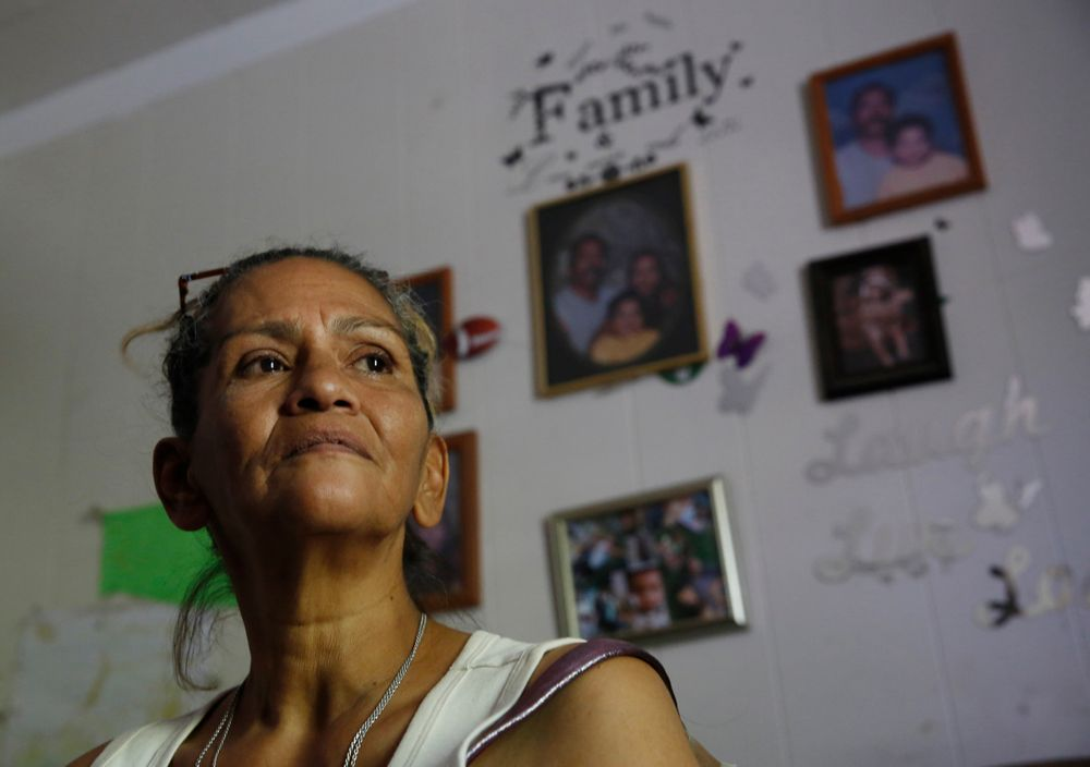 In this photo taken Wednesday, Aug. 14, 2019, Susie Garza, who receives a city provided debit card through the Stockton Economic Empowerment Demonstration she receives monthly through a trial program poses in her home in Stockton, Calif. The program, which started in February, gives $500 a month to 125 people who earn at or below the median household income of $46,033. They can spend the money with no restrictions. Stockton Mayor Michael Tubbs, who initiated the privately funded program, says it could be a solution to the city's poverty problem. (AP Photo/Rich Pedroncelli)