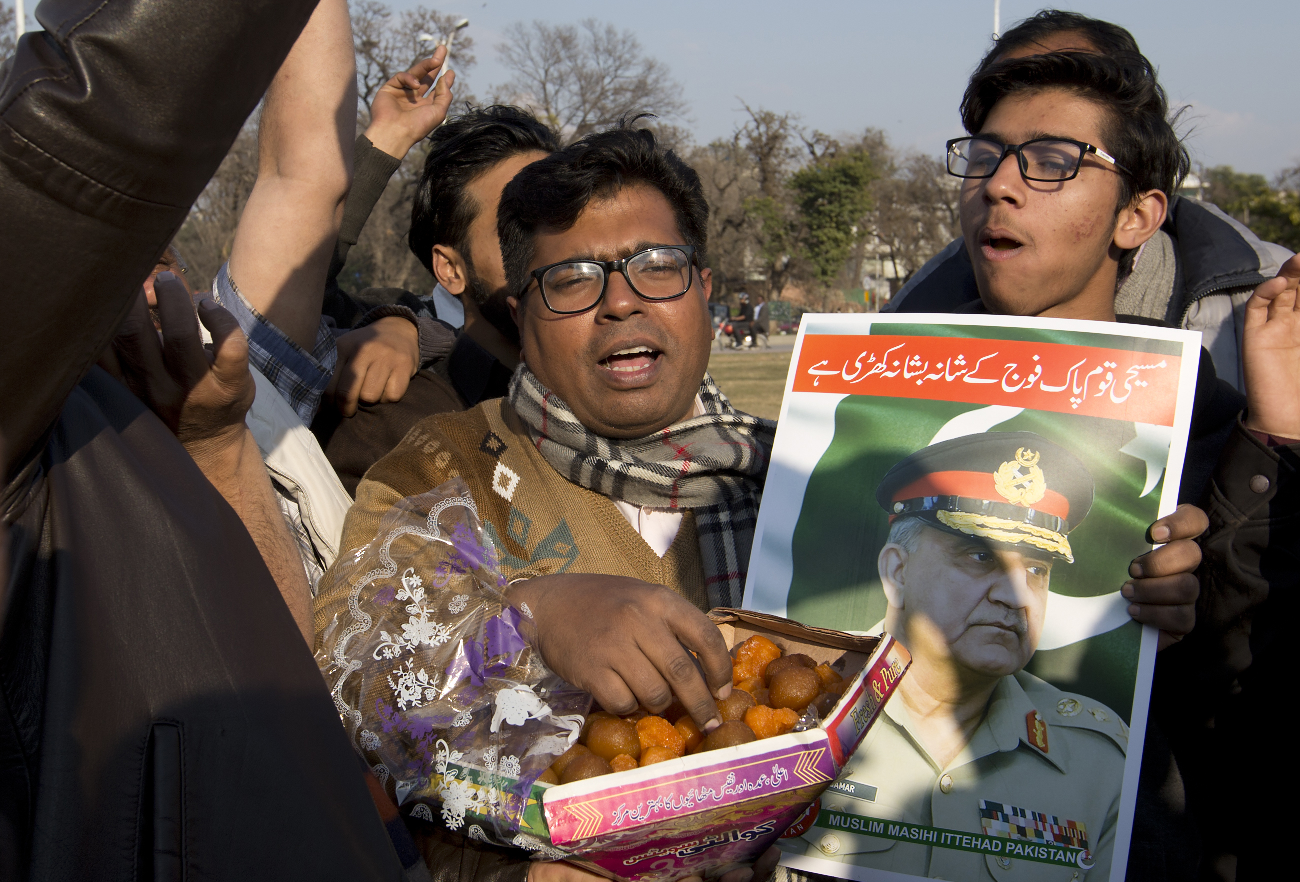 People holding a poster of Pakistani army chief exchange sweets to celebrate the shooting down Indian planes by Pakistani forces, outside in Islamabad, Pakistan, Wednesday, Feb. 27, 2019. Pakistan's military said Wednesday it shot down two Indian warplanes in the disputed region of Kashmir and captured two pilots, raising tensions between the nuclear-armed rivals to a level unseen in 20 years. (AP Photo/B.K. Bangash)