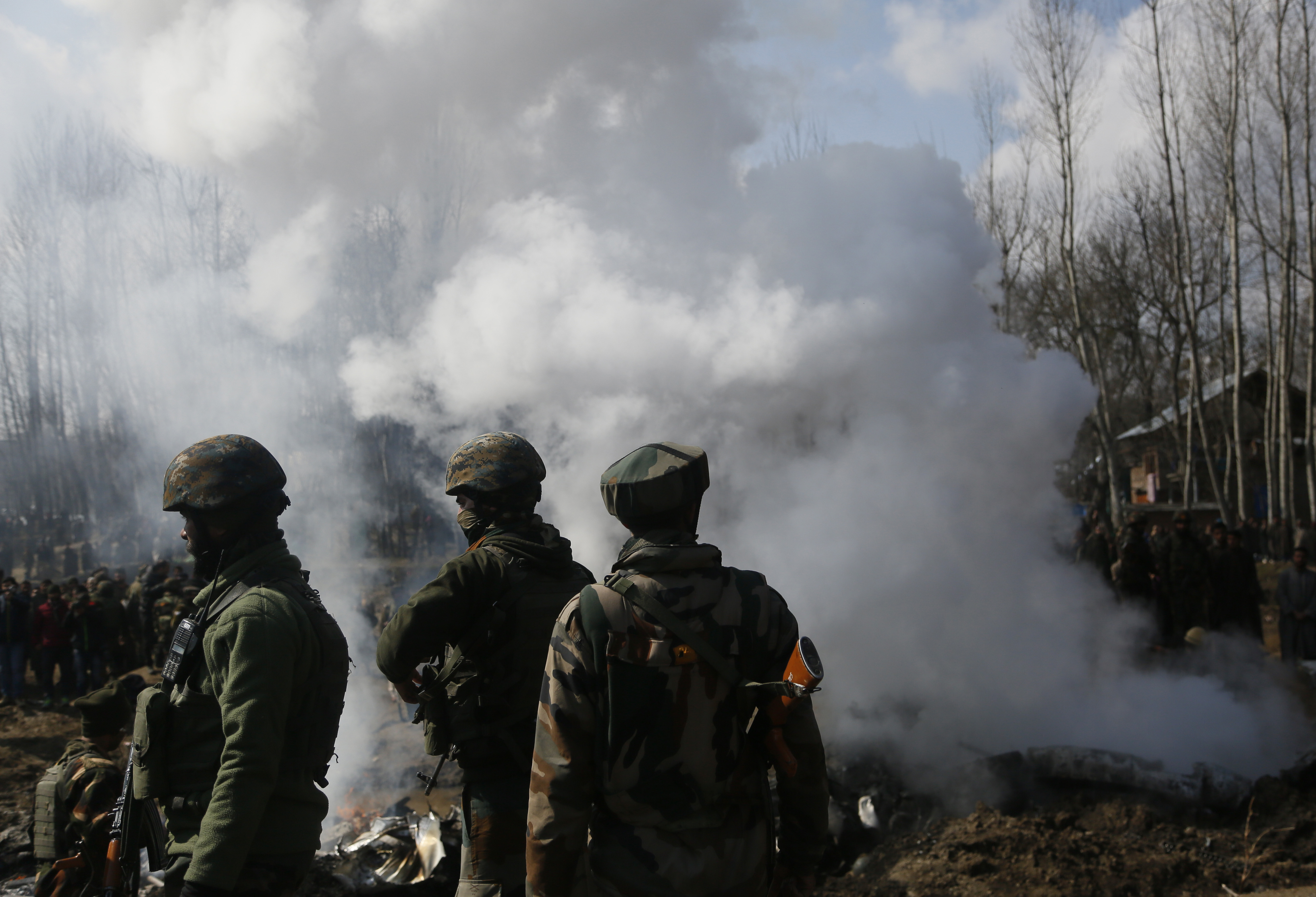 Indian army soldiers stand near the wreckage of an Indian aircraft after it crashed in Budgam area, outskirts of Srinagar, Indian controlled Kashmir, Wednesday, Feb.27, 2019. (AP Photo/Mukhtar Khan)