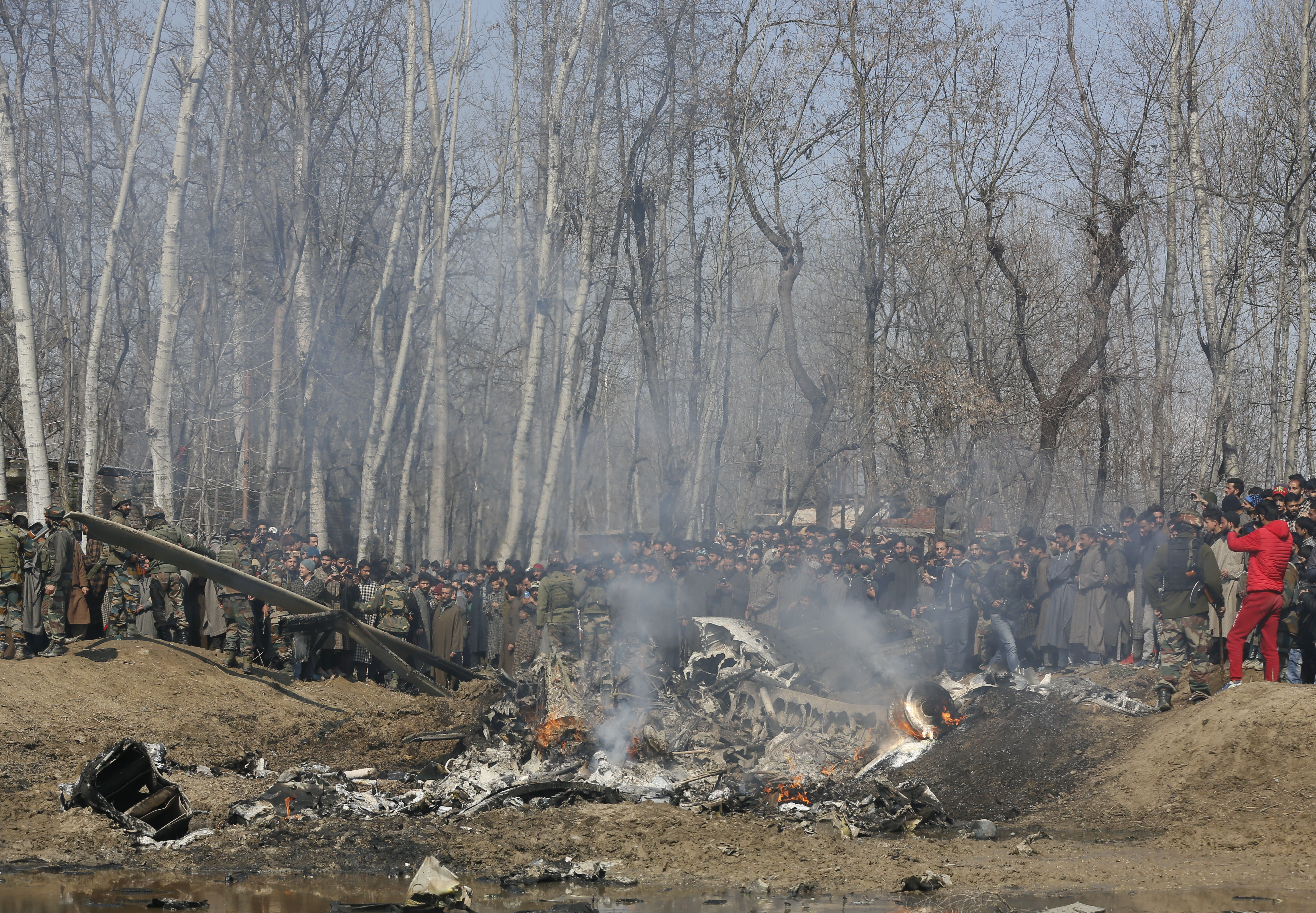 Kashmiri villagers gather near the wreckage of an Indian aircraft after it crashed in Budgam area, outskirts of Srinagar, Indian controlled Kashmir, Wednesday, Feb.27, 2019. (AP Photo/Mukhtar Khan)