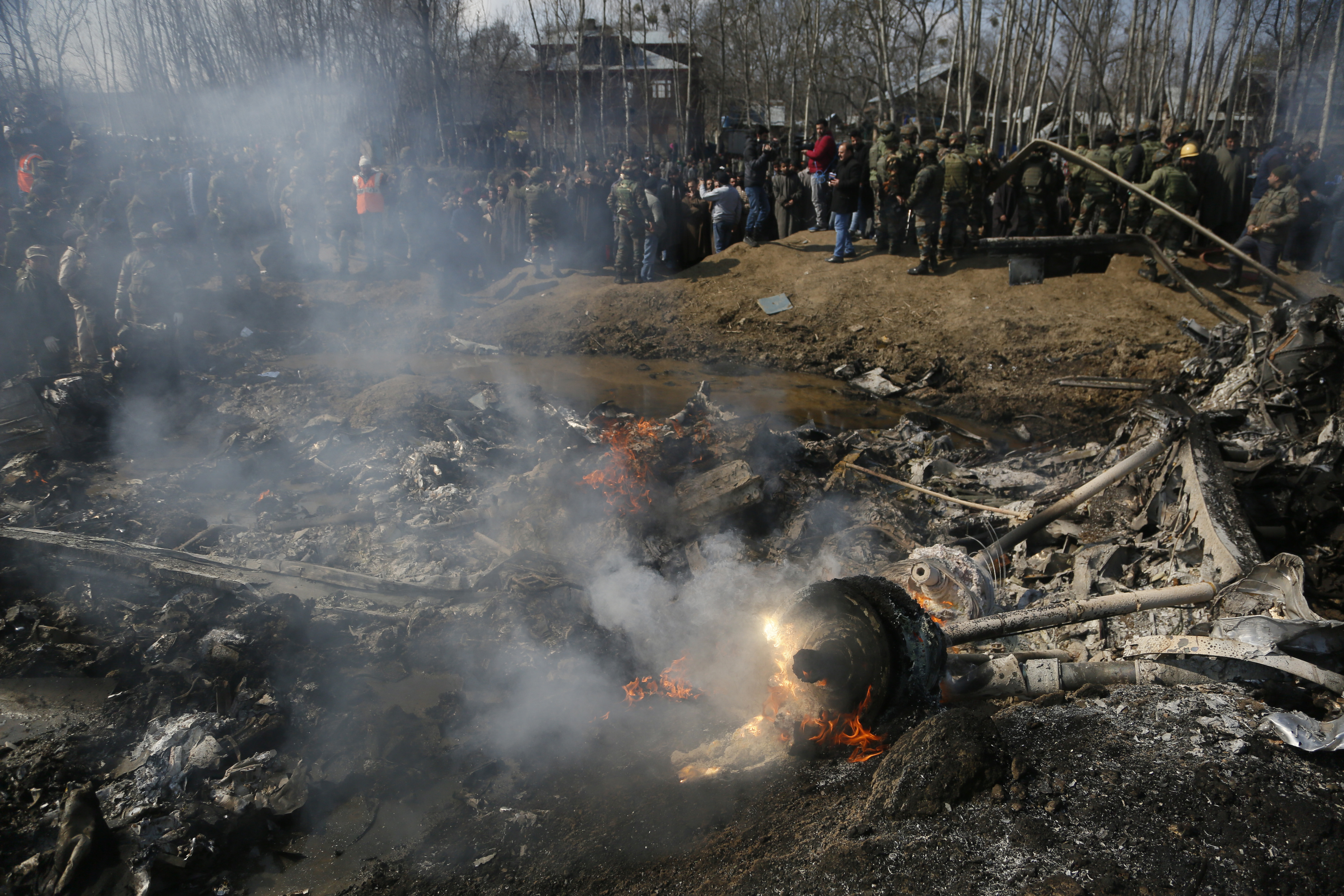 Kashmiri villagers and Indian army soldiers gather near  the wreckage of an Indian aircraft after it crashed in Budgam area, outskirts of Srinagar, Indian controlled Kashmir, Wednesday, Feb.27, 2019. (AP Photo/Mukhtar Khan)