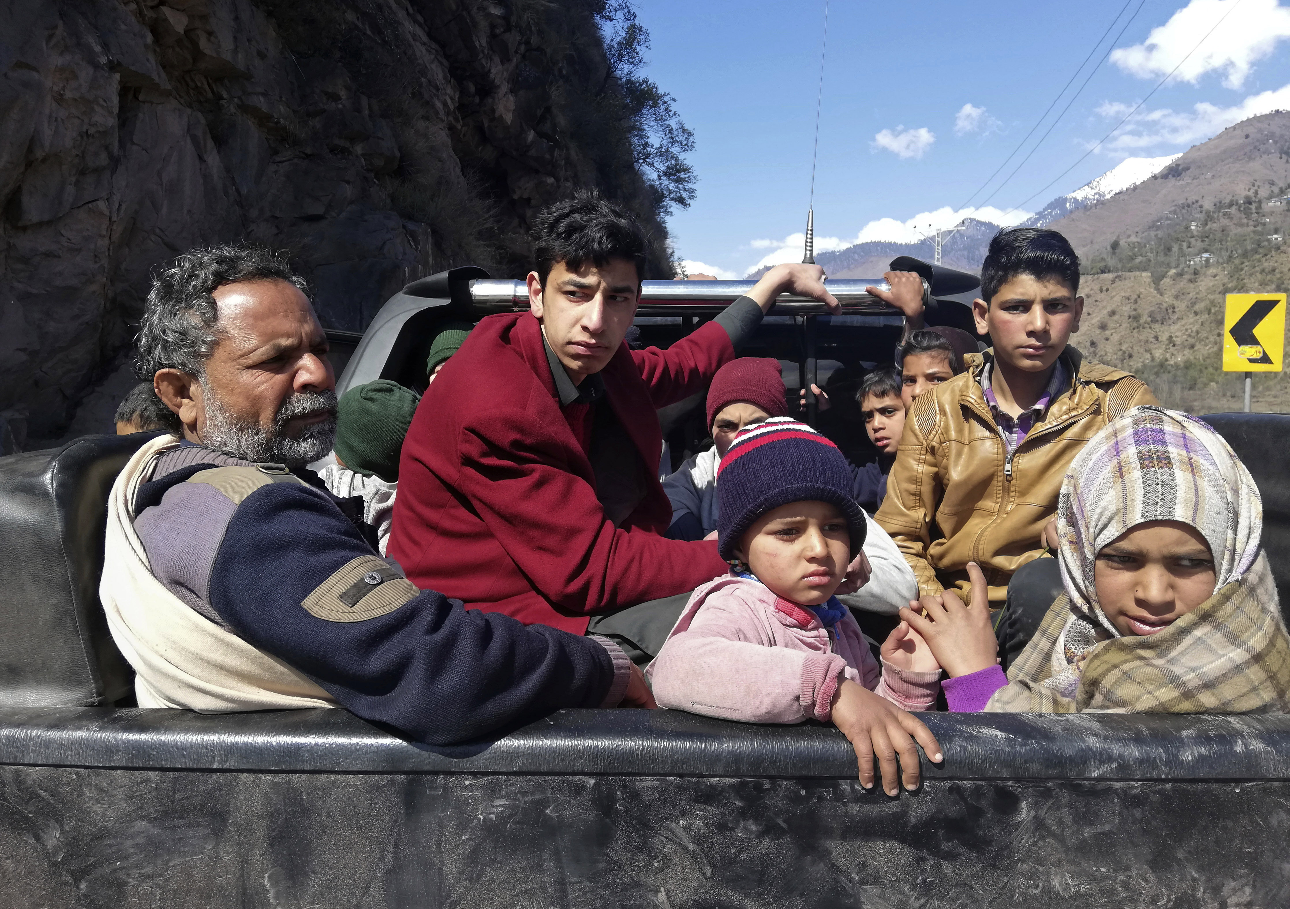 Pakistani Kashmiris flee the town of Chakoti which is about 3 miles, 5 km, from the Pakistan Indian border, following the intense exchange of fire between Pakistan and India, at the Line of Control in Pakistani Kashmir, Wednesday, Feb. 27, 2019. Pakistan's military said Wednesday it shot down two Indian warplanes in the disputed region of Kashmir and captured two pilots, raising tensions between the nuclear-armed rivals to a level unseen in 20 years. (AP Photo/M.D. Mughal)
