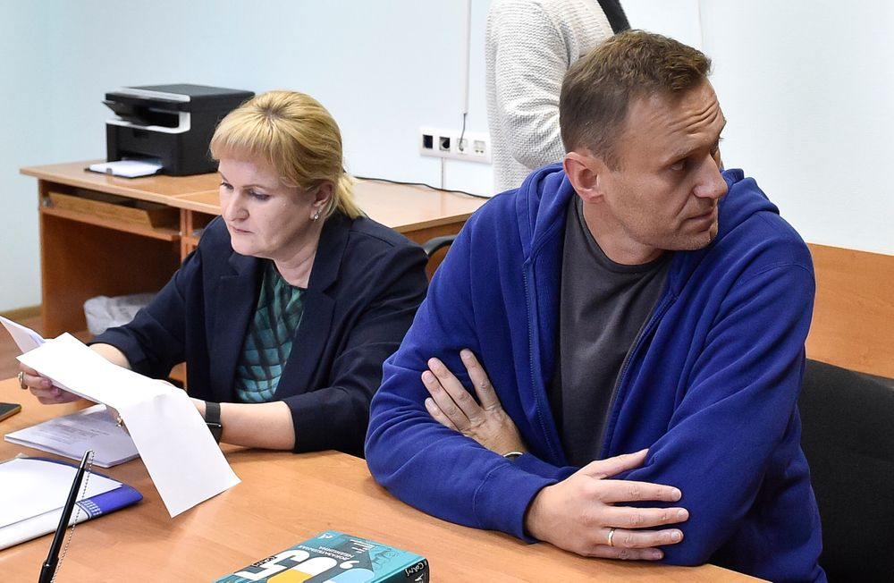 Alexei Navalny, Russia's most prominent opposition figure, who has been detained by police and charged with unlawfully organizing a public gathering, sits in a court room as his lawyer Olga Mikhailova, left, reads documents in Moscow, Russia, Wednesday, July 24, 2019. Navalny has called for demonstrators to protest on Saturday outside the mayor's office against the rejection of several opposition candidates from the ballot for this fall's Moscow city council elections. (AP Photo/Dmitry Serebryakov)