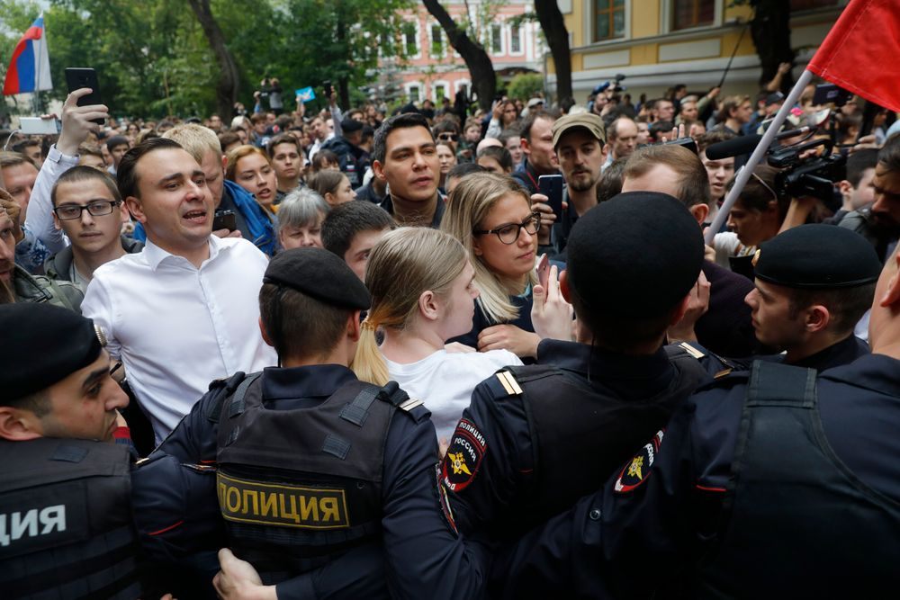 Russian opposition candidate and lawyer at the Foundation for Fighting Corruption Lyubov Sobol, center, and candidate Ivan Zhdanov, 2nd left, stand with other protesters in front of police line during a protest in Moscow, Russia, Sunday, July 14, 2019. Around 1,000 people have gathered in central Moscow to demand that opposition candidates be included on ballots for an upcoming city parliament election in September. (AP Photo/Pavel Golovkin)