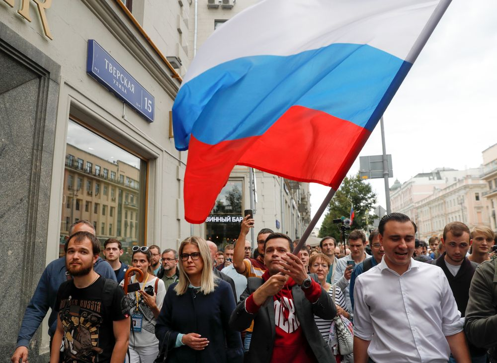 Russian opposition candidate Ilya Yashin, center right, and opposition candidate and lawyer at the Foundation for Fighting Corruption Lyubov Sobol, center left, walk during a protest in Moscow, Russia, Sunday, July 14, 2019. Opposition candidates who run for seats in the city legislature in September's elections have complained that authorities try to bar them from the race by questioning the validity of signatures of city residents they must collect in order to qualify for the race. (AP Photo/Pavel Golovkin)