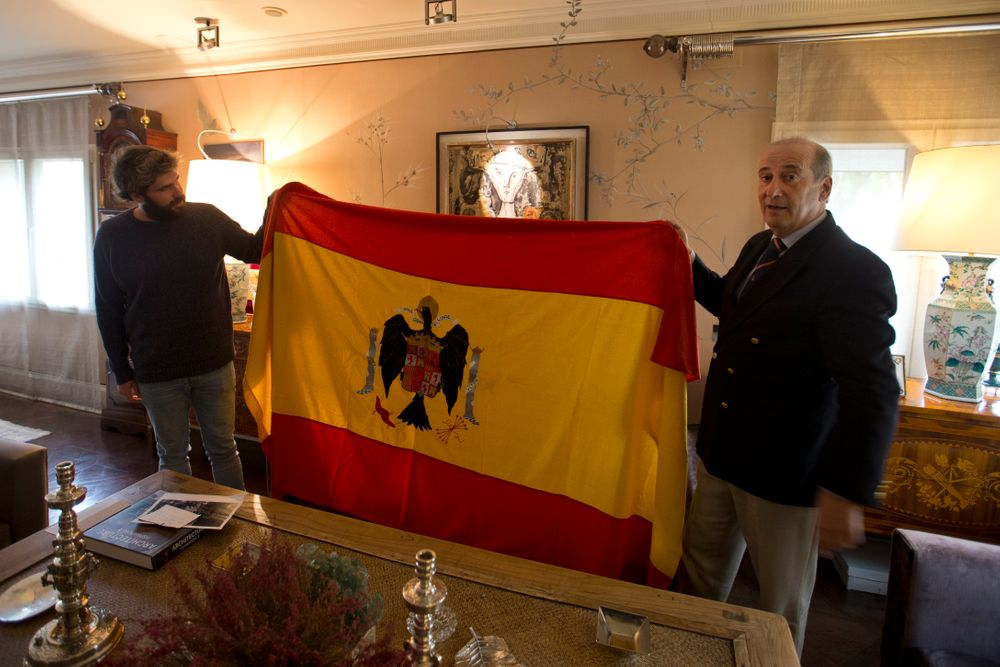 Spanish dictator General Francisco Franco's grandson, Francisco Franco Martinez-Bordiu, right, and his son Alvaro hold up a pre-constitutional Spanish flag they want draped over the coffin General Franco during his reburial Thursday after an interview with The Associated Press in Madrid, Spain, Wednesday, Oct. 23, 2019. Weather permitting, the Spanish dictator's preserved body will be flown Thursday by helicopter to the Franco family's private chapel in the Mingorrubio cemetery. It's a discrete site compared to the Valley of the Fallen, a vainglorious mausoleum and basilica that Franco built and where he was buried in 1975. The complex, which is topped by a 152-meter (500-foot) granite cross that can be seen for miles, still remains a National Heritage site. (AP Photo/Paul White)
