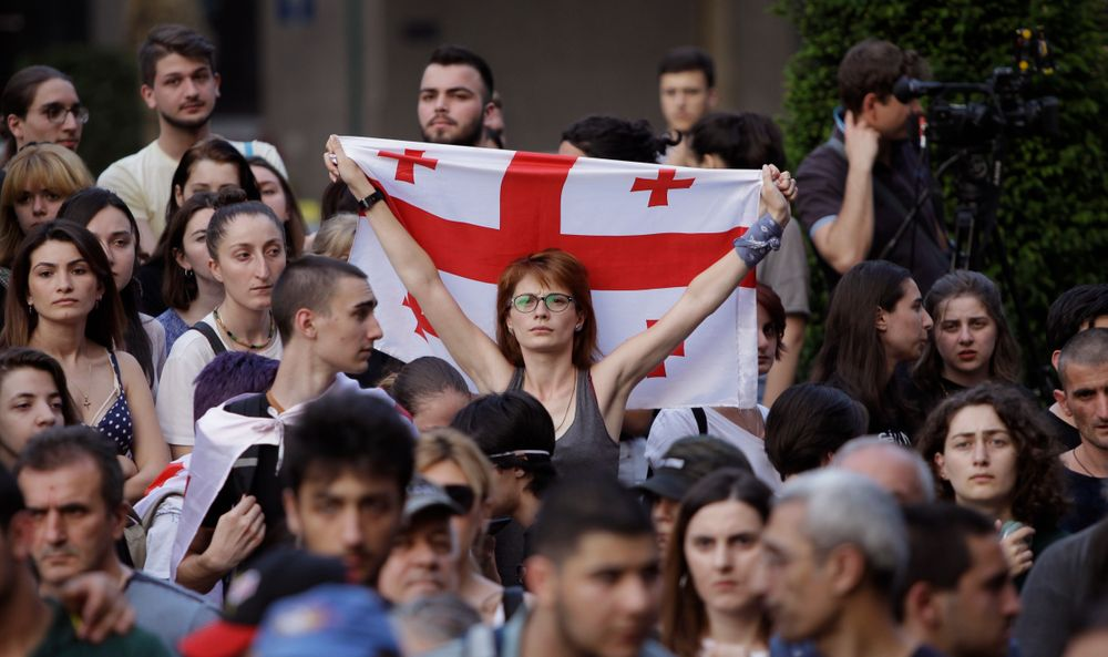 A woman holds a Georgian national flags as opposition demonstrators gather in front of the Georgian Parliament building in Tbilisi, Georgia, Saturday, June 22, 2019. Demonstrators denounced the government Friday as overly friendly to Russia and calling for a snap parliamentary election. (AP Photo/Shakh Aivazov)