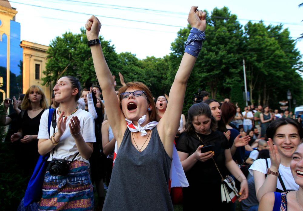 Young opposition demonstrators react while listening an orator as they gather in front of the Georgian Parliament building in Tbilisi, Georgia, Saturday, June 22, 2019. Demonstrators denounced the government Friday as overly friendly to Russia and calling for a snap parliamentary election. (AP Photo/Shakh Aivazov)