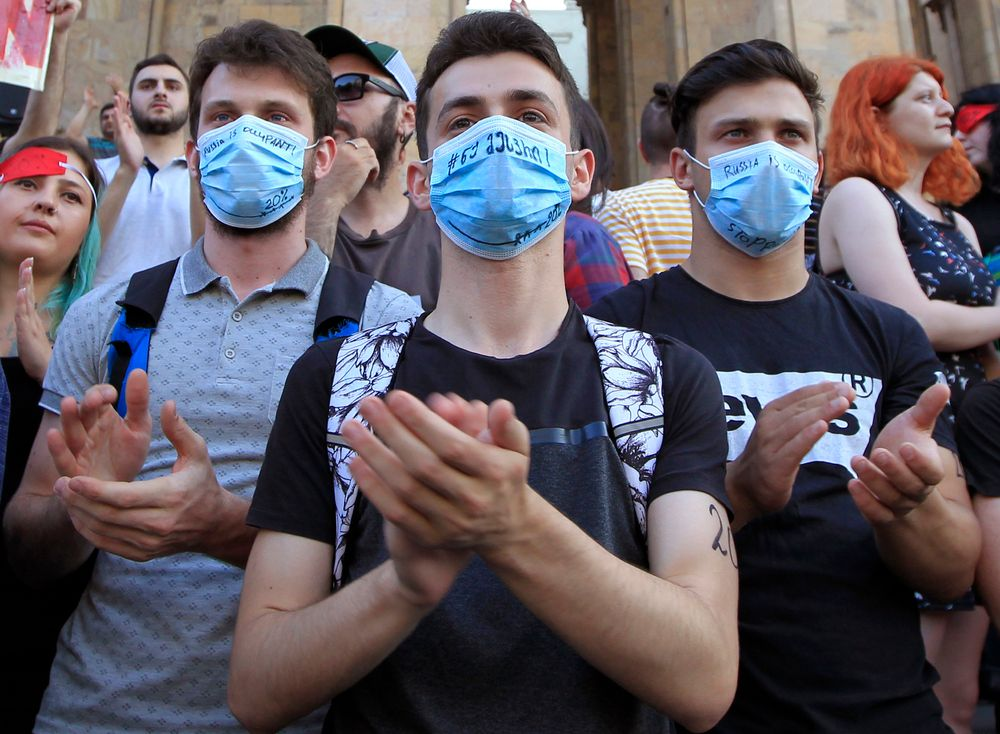 Young opposition demonstrators wearing masks reading
