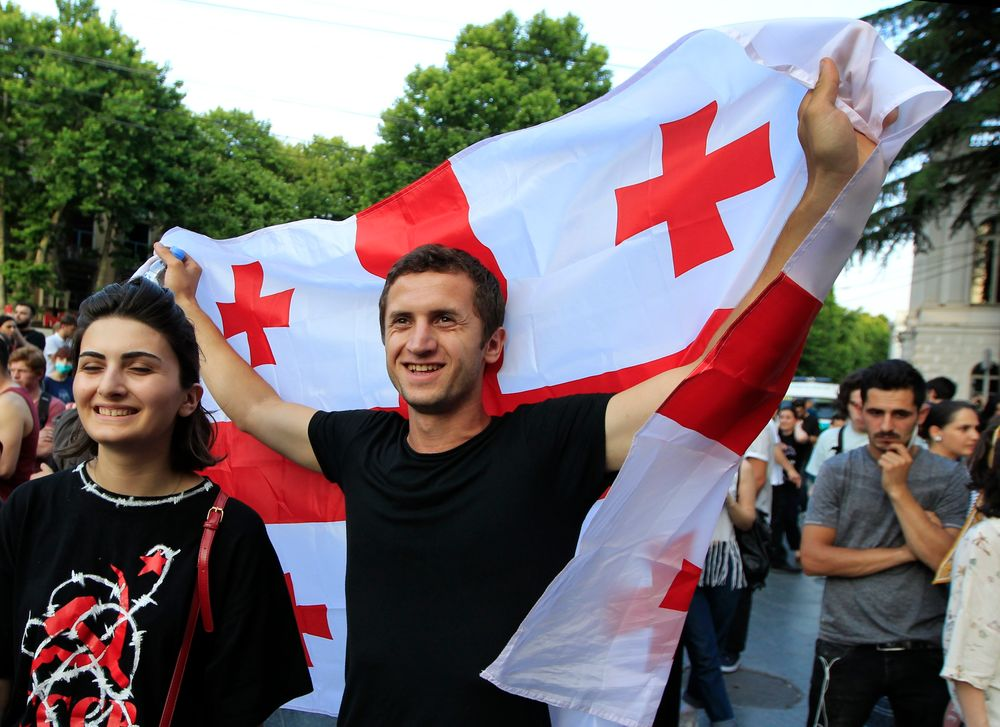 A man holds a Georgian national flags as opposition demonstrators gather in front of the Georgian Parliament building in Tbilisi, Georgia, Saturday, June 22, 2019. Demonstrators denounced the government Friday as overly friendly to Russia and calling for a snap parliamentary election. (AP Photo/Shakh Aivazov)