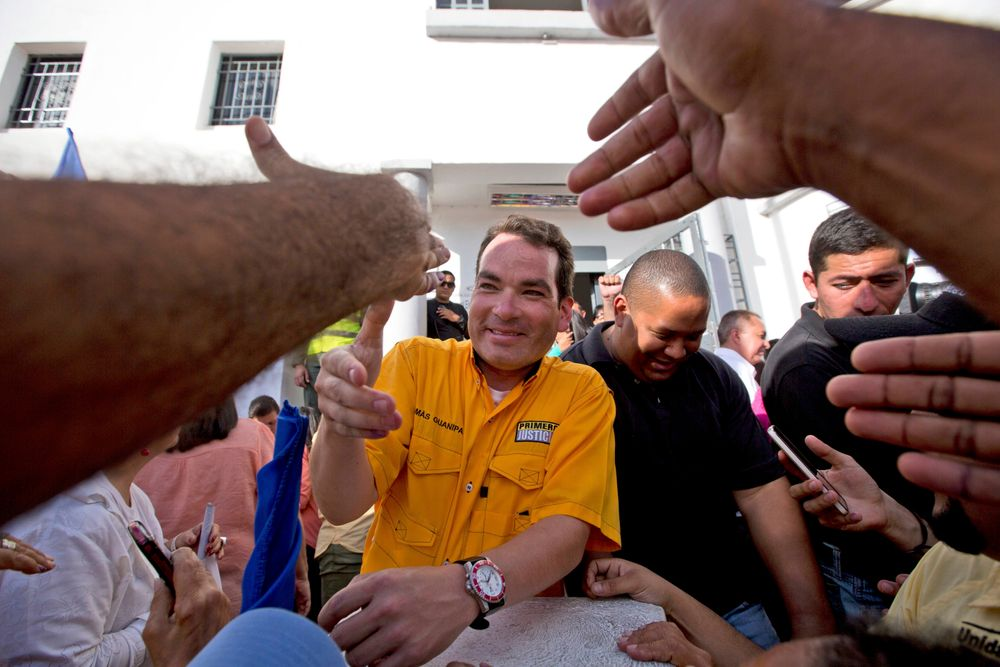 FILE - In this Dec. 9, 2015 file photo, reelected opposition congressman Tomas Guanipa greets supporters outside the National Electoral Council in Caracas, Venezuela. On Monday, Aug. 12, 2019, Venezuela's supreme court stripped Guanipa and two other opposition lawmakers of immunity from prosecution as accused traitors amid rising political tension in the crisis-stricken nation. (AP Photo/Fernando Llano, File)