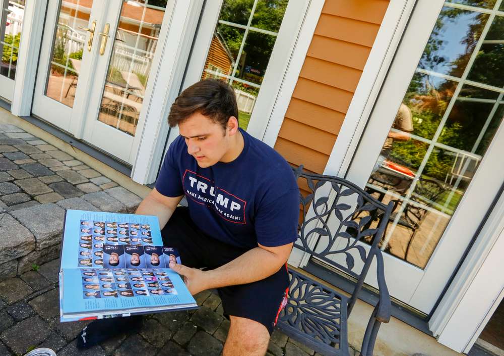FILE - In this June 9, 2017, file photo, Grant Berardo, a student at Wall High School, flips through his 2017 school yearbook in Wall, N.J. The yearbook includes a photo of him wearing a digitally altered T-shirt that originally included the words